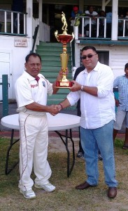 Upper East Coast Tigers' skipper Sheik Mohamed receives the championship trophy from sponsor Raj Singh